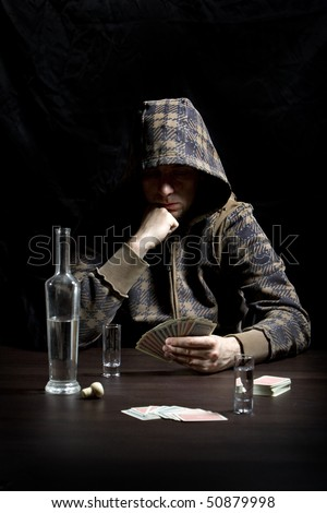 Young man with hood, drinking alcohol and gambling