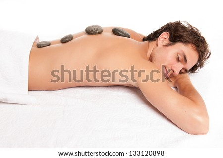 Young man with hot stones on the back