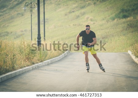 young man with inline skates ride in summer park outdoor roller skater #461727313