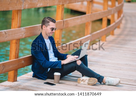 Young man with laptop drinking coffee outdoors. Happy boy working by notebook outdoor in the city