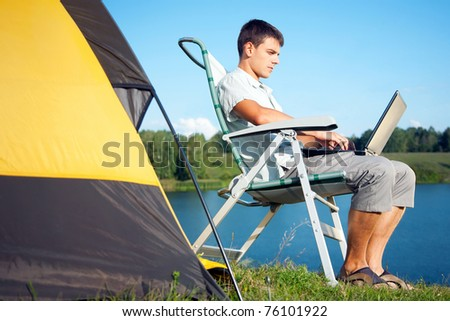 young man with laptop near the tent