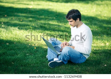 Young man with laptop outdoor sitting on the grass