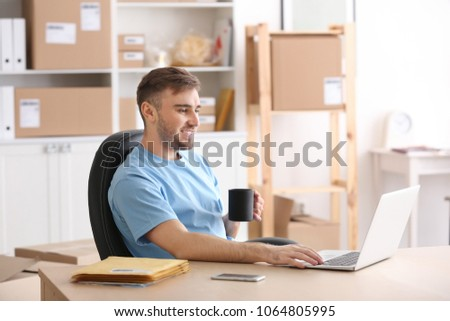 Young man with laptop preparing parcels for shipment to client in home office