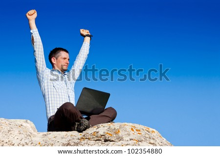 Young man with laptop Sits and Celebrates Outdoors