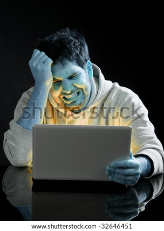 Young man with laptop under strange light and glowing yellow from screen