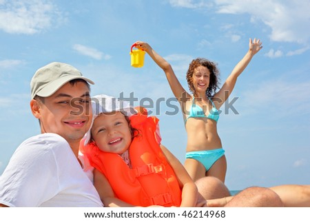 young man with little girl in orange life-jacket and beautiful woman with plastic toy bucket, woman lifted hands upwards