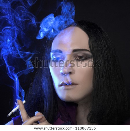 Young man with long black hair smoking cigarette