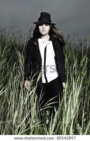 Young man with long brown hair wearing black suit and black hat standing in field with long grass. Stormy cloudy sky.