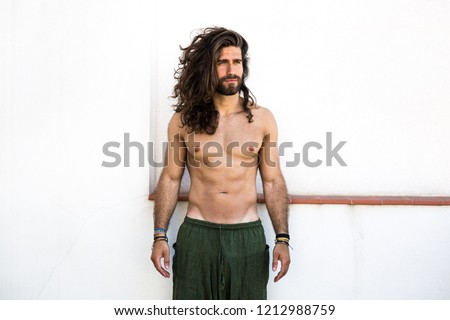 Young man with long hair posing with a white background