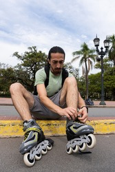 young man with long hair tying his rollers in a park. dispersion time. exercise for health. olympic sport.