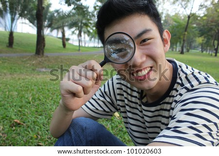 Young man with magnify glass