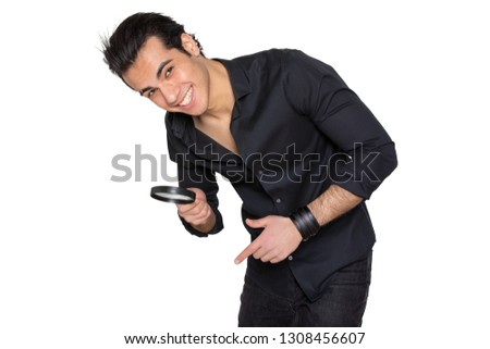 young man with magnifying glass looking down the frame on an isolated background. smiles and rejoices in the discovery and shows on the discovery of a finger
