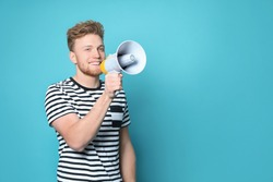 Young man with megaphone on color background. Space for text