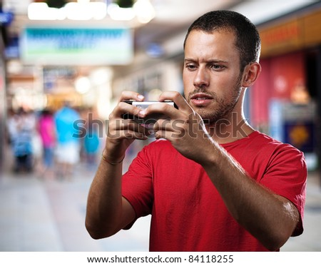 young man with mobile phone at shopping center