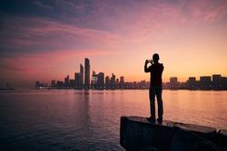 Young man with mobile phone photographing urban skyline at sunrise. Abu Dhabi, United Arab Emirates.