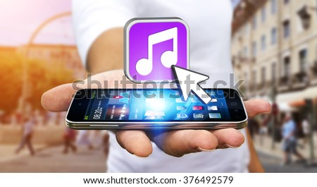 Young man with modern mobile phone in his hand using modern music application #376492579