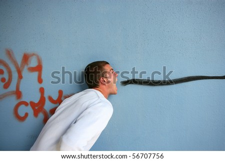 Young man with mouth open face to a graffiti