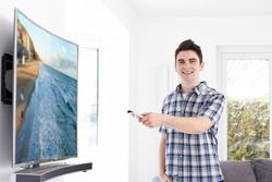 Young Man With New Curved Screen Television At Home