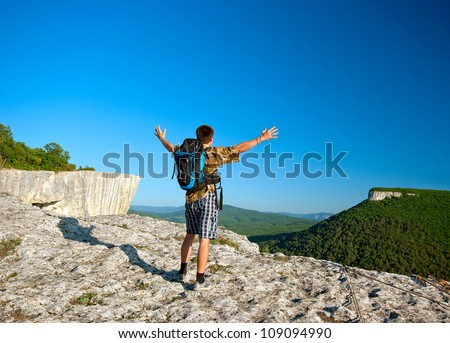 young man with open arms at the top of the mountain