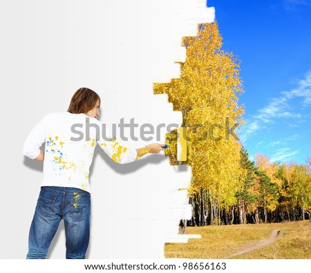 Young man with paint brush and wall with natural landscape