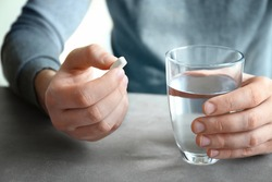 Young man with pill and glass of water at home, closeup