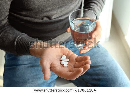 Young man with pills and glass of water at home, closeup #619881104