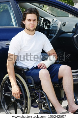 Young man with plaster cast after an accident in wheelchair arriving or leaving the hospital, car with opened door in the background.