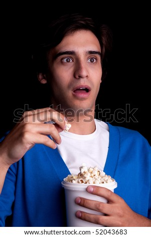young man, with popcorn watching, on black background. Studio shot