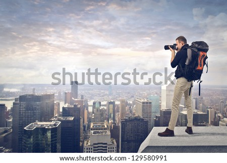 young man with professional camera photographing the city from the top #129580991