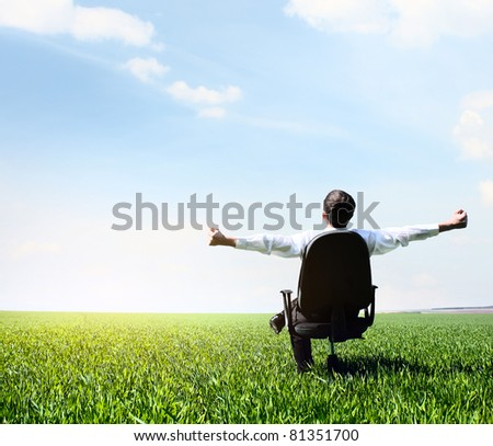 Young man with raised hands sitting in char on green meadow and looking to a sky with clouds #81351700