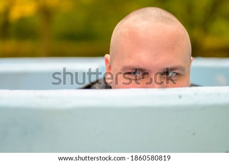 Young man with shaved head hunkering down in an outdoor tub or pool peering over the rim glancing to the side Stockfoto ©