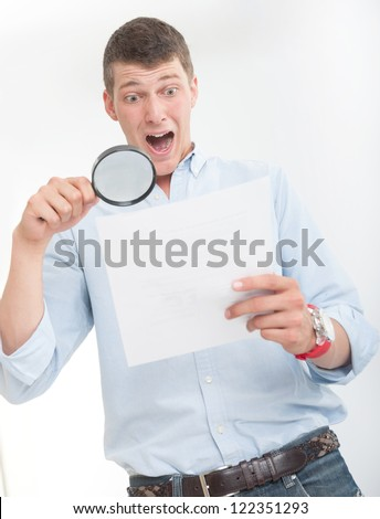 Young man with shocked expression examining a document through a magnifying lens