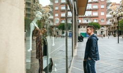 Young man with shopping bags looking at a shop window to buy a gift