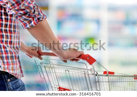 Young man with shopping cart in store