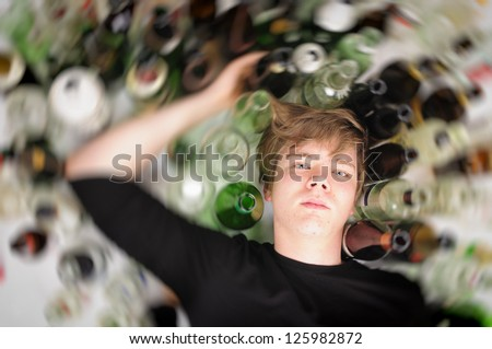 Young man with short blond hair lying on the floor and is surrounded by many empty beer and liquor bottles, upper perspective.