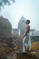 Young man with shredded body wearing dhoti, praying in the temple early in the morning.