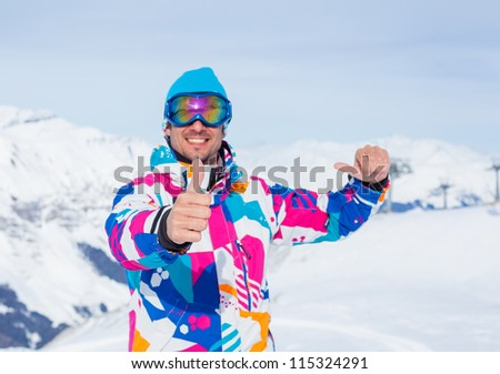Young man with skis and a ski outfit in the Zillertal Arena, Austria. Focus on the finger