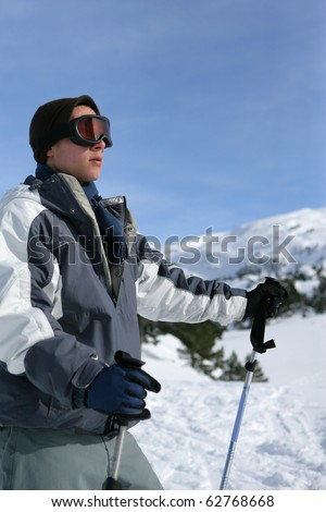 Young man with skis in snowy landscape