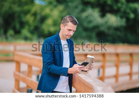 Young man with smartphone drinking coffee outdoors. Happy boy working by cellphone outdoor in the city