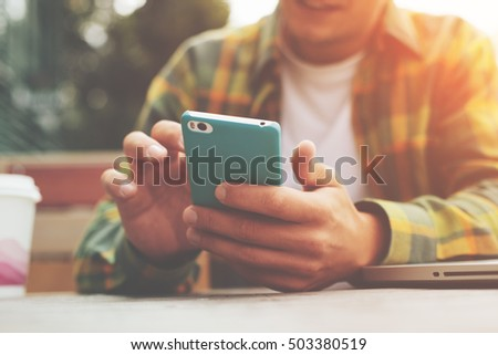 Young man with smartphone in hand sitting in street cafe, texting with friends #503380519