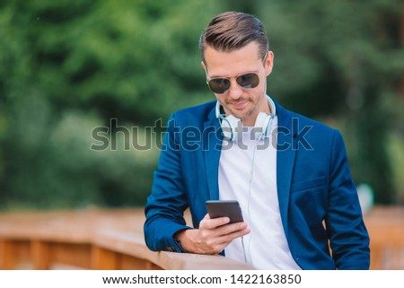 Young man with smartphone outdoors. Happy boy working by cellphone outdoor in the city