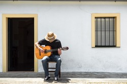 Young man with straw hat playing classical guitar in front of the facade of his white house in the countryside on a sunny day. Rural lifestyle.
