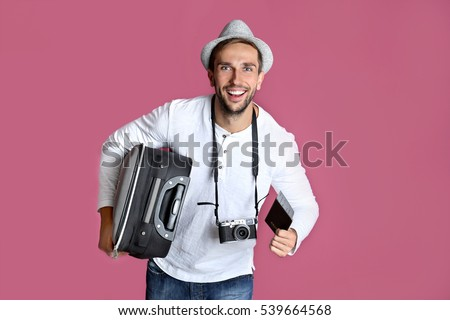 Young man with suitcase, camera and ticket on purple background #539664568