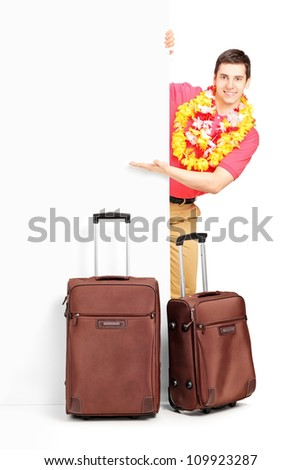 Young man with suitcases posing behind panel isolated on white background
