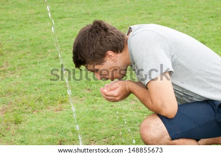 Young man with sweaty, muddy face getting refreshment from running water on a hot summer day