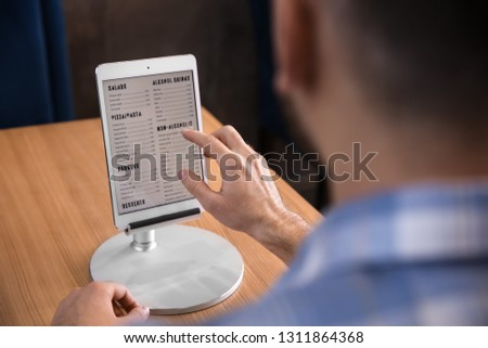 Young man with tablet PC looking through menu in restaurant #1311864368