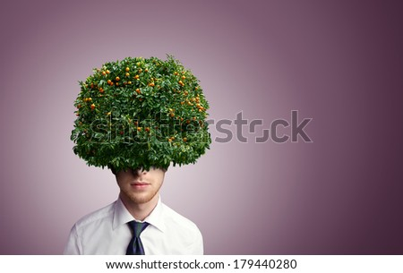 Young man with tangerine tree instead hair