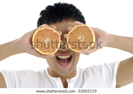 Young man with tropical fruit halves over eyes smiling