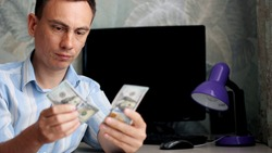 Young man with upset face is counting money cash. A businessman counting US dollar bills and holding his head.