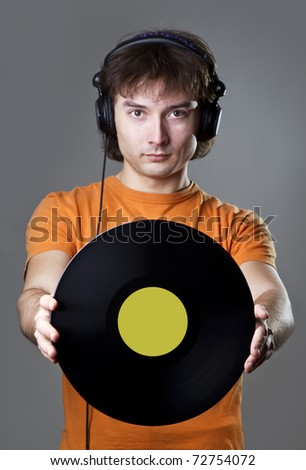Young man with vinyl record and headphones